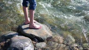 Ποταμός βουνών Ο τύπος στέκεται σε έναν βράχο, τις ροές του νερού περίπου τα πόδια του και την πέτρα Ταξιδιώτης ξημερωμάτων απόθεμα βίντεο
