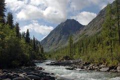 Ποταμός βουνών που περιβάλλεται από τις υψηλές αιχμές Στοκ εικόνα με δικαίωμα ελεύθερης χρήσης