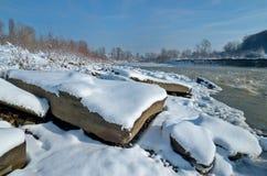 Ποταμός βουνών το χειμώνα με τους μεγάλους βράχους στο πρώτο πλάνο Στοκ Φωτογραφίες