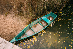 Ποταμός και αλιευτικό σκάφος κωπηλασίας κοντά στο κόστος στην εποχή φθινοπώρου Στοκ Εικόνες