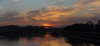 Ποταμός και γέφυρα στο χρόνο ηλιοβασιλέματος, το φωταγωγό στην αυγή και το λυκόφως Στοκ Εικόνα