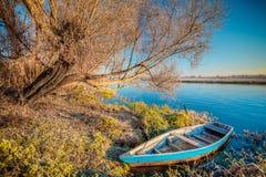 Ποταμός και παλαιό ξύλινο αλιευτικό σκάφος κωπηλασίας Στοκ Εικόνες