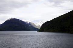 Ποταμός και χιονώδη βουνά - σκοτεινή θυελλώδης ημέρα στοκ εικόνες