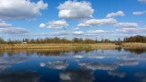 Ποταμός με τα δέντρα και τα σύννεφα στην αντανάκλαση Στοκ Φωτογραφία