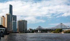 Ποταμός πόλεων του Μπρίσμπαν Αυστραλία με τη γέφυρα ιστορίας στην ημέρα και τα σύννεφα στοκ φωτογραφία