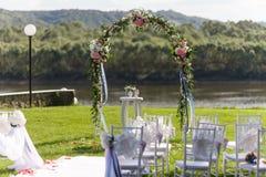 Ποταμός Ρομαντική γαμήλια τελετή Άσπρες ξύλινες καρέκλες με την κορδέλλα και λουλούδια σε έναν πράσινο χορτοτάπητα Πολυθρόνες της Στοκ φωτογραφία με δικαίωμα ελεύθερης χρήσης