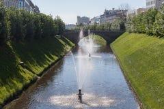 Ποταμός στο κέντρο της πόλης το κανάλι ποταμών με τη γέφυρα και τις πηγές Στοκ Εικόνες