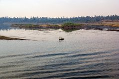 Ποταμός του Νείλου με το σύνολο τραπεζών των δέντρων και της βλάστησης και των αιγυπτιακών ψαράδων στις χαρακτηριστικές βάρκες κω Στοκ Εικόνα