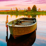 Ποταμός φθινοπώρου ή λίμνη και παλαιά πράσινη βάρκα κωπηλασίας Στοκ Φωτογραφίες