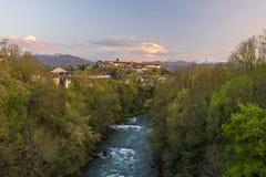 Ποταμός Oloron και πόλη oloron-Sainte-Marie στο φως ηλιοβασιλέματος Τα βουνά των γαλλικών ατλαντικών Πυρηναίων είναι στο υπόβαθρο στοκ εικόνα με δικαίωμα ελεύθερης χρήσης