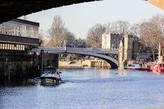 Ποταμός Ouse με την πηγαίνοντας βάρκα και όχθη ποταμού στην Υόρκη, Μεγάλη Βρετανία στην ηλιόλουστη χειμερινή ημέρα στοκ φωτογραφία