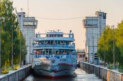 Ποταμός Sheksna, Ρωσία - 07 19 2018: Το κρουαζιερόπλοιο δύο επιβατών κεφάλαια περνά μέσω της πύλης του φράχτη στο Sheksna στοκ εικόνα