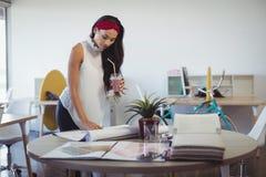 Ποτό εκμετάλλευσης επιχειρηματιών εργαζόμενος στο γραφείο γραφείων Στοκ εικόνες με δικαίωμα ελεύθερης χρήσης