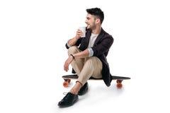 Ποτό κατανάλωσης ατόμων από το plasic φλυτζάνι καθμένος skateboard που απομονώνεται στο λευκό Στοκ εικόνες με δικαίωμα ελεύθερης χρήσης