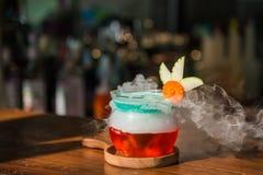 Ποτό κοκτέιλ υπέρ με τον καπνό στο ξύλινο πιάτο στοκ φωτογραφίες
