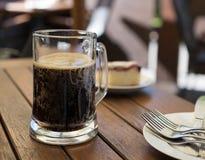 Ποτό κόλας σε ένα γυαλί με το κέικ για ένα αναζωογονώντας θερινό ποτό Στοκ εικόνα με δικαίωμα ελεύθερης χρήσης