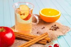 Ποτό της Apple σε ένα γυαλί με ένα μήλο και πορτοκάλι σε ένα υπόβαθρο colubrum Στοκ Εικόνες