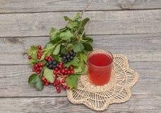Ποτό του viburnum και του aronia σε ένα ξύλινο υπόβαθρο Στοκ εικόνα με δικαίωμα ελεύθερης χρήσης