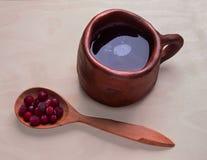 Ποτό των βακκίνιων σε μια μεγάλη κούπα αργίλου και φρέσκα μούρα στο ξύλινο κουτάλι Στοκ Εικόνες