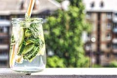 Ποτό Detox από το αγγούρι, το λεμόνι και τη μέντα στο υπόβαθρο μιας σύγχρονης πόλης νεολαίες ενηλίκων Στοκ Εικόνες