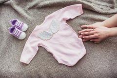 Πουκάμισο μωρών στον καναπέ με τα παπούτσια και moms το χέρι Στοκ Εικόνες