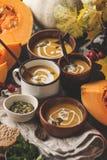 Πουρές σούπας κολοκύθας φθινοπώρου με την κρέμα στα φλυτζάνια, το τοπίο φθινοπώρου στοκ εικόνες
