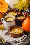 Πουρές σούπας κολοκύθας φθινοπώρου με την κρέμα στα φλυτζάνια, το τοπίο φθινοπώρου στοκ φωτογραφίες με δικαίωμα ελεύθερης χρήσης