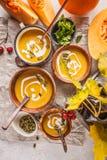 Πουρές σούπας κολοκύθας φθινοπώρου με την κρέμα στα φλυτζάνια, το τοπίο φθινοπώρου στοκ εικόνα