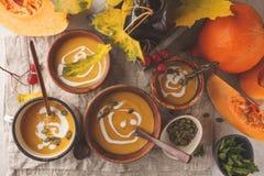 Πουρές σούπας κολοκύθας φθινοπώρου με την κρέμα στα φλυτζάνια, το τοπίο φθινοπώρου στοκ φωτογραφία