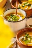 Πουρές σούπας κολοκύθας φθινοπώρου με την κρέμα στα φλυτζάνια, το τοπίο φθινοπώρου στοκ φωτογραφίες
