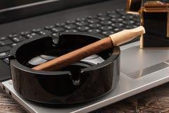 Πούρο κινηματογραφήσεων σε πρώτο πλάνο ashtray που στέκεται σε ένα lap-top Στοκ φωτογραφίες με δικαίωμα ελεύθερης χρήσης
