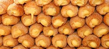 Πολλά κέικ και το cannoli αποβουτυρώνουν για την πώληση στη ζύμη Στοκ Εικόνες