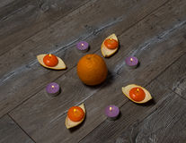 Πολλά καίγοντας πορτοκαλιά και πορφυρά στρογγυλά κεριά με το πορτοκάλι Στοκ Εικόνα
