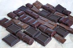 Πολλά κομμάτια των φραγμών σοκολάτας των διαφορετικών τύπων και των μορφών σχεδιάζονται τσαλακωμένο στο φως χαρτί Στοκ Φωτογραφίες