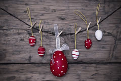 Πολλά κόκκινα και άσπρα αυγά Πάσχας και ένα μεγάλο αυγό που κρεμούν το σε απευθείας σύνδεση πλαίσιο Στοκ Φωτογραφία