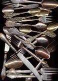 Πολλά παλαιά κουτάλια, μαχαίρια, δίκρανα στο μαύρο υπόβαθρο Στοκ εικόνες με δικαίωμα ελεύθερης χρήσης