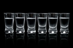 Πολλά ποτήρια της βότκας που απομονώνεται στο μαύρο υπόβαθρο Στοκ Εικόνα