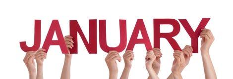 Πολλά χέρια ανθρώπων κρατούν το κόκκινο ευθύ Word Ιανουάριος Στοκ Εικόνες