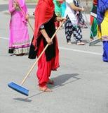 πολλές ξυπόλυτες γυναίκες με τα ζωηρόχρωμα ενδύματα σκουπίζουν το στρωμένο δρόμο α στοκ εικόνες