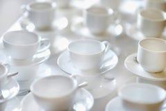 Πολλές σειρές των καθαρών άσπρων φλυτζανιών και των πιατακιών Στοκ φωτογραφίες με δικαίωμα ελεύθερης χρήσης