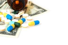 Πολλές χάπια και ταμπλέτες στο λογαριασμό δολαρίων που απομονώνεται στο άσπρο backgrou Στοκ εικόνα με δικαίωμα ελεύθερης χρήσης
