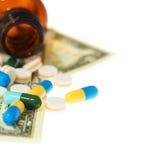 Πολλές χάπια και ταμπλέτες στο λογαριασμό δολαρίων που απομονώνεται στο άσπρο backgrou Στοκ Εικόνα