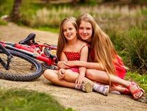 Ποδήλατα που ανακυκλώνουν τα παιδιά που κάθονται το δρόμο κοντά στα ποδήλατα Στοκ εικόνα με δικαίωμα ελεύθερης χρήσης