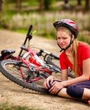 Ποδήλατα που ανακυκλώνουν το κορίτσι που φορά το κράνος Το παιδί έπεσε από το ποδήλατο Στοκ φωτογραφία με δικαίωμα ελεύθερης χρήσης