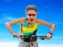 Ποδήλατα που ανακυκλώνουν το κορίτσι που φορά το ποδήλατο γύρων κρανών ενάντια στο μπλε ουρανό Στοκ εικόνες με δικαίωμα ελεύθερης χρήσης