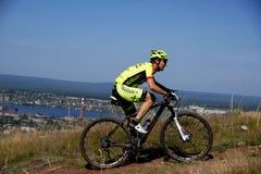 Ποδήλατο βουνών δρομέων ανηφορικό ενάντια στον ουρανό Στοκ Εικόνες