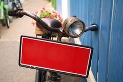 Ποδήλατο με το κόκκινο δοχείο λουλουδιών εμβλημάτων φέρνοντας Στοκ Φωτογραφίες