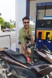 Ποδήλατο μηχανών καυσίμων ατόμων, ευτυχής ισπανικός τύπος χαμόγελου στο βενζινάδικο Στοκ Εικόνα