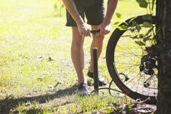 ποδήλατο που διογκώνει τη ρόδα Ο ποδηλάτης επισκευάζει το ποδήλατο στο δασικό αντλώντας αέρα Bicyclist στη ρόδα Ο ποδηλάτης χρησι Στοκ φωτογραφία με δικαίωμα ελεύθερης χρήσης