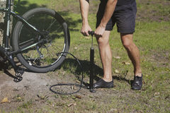 ποδήλατο που διογκώνει τη ρόδα Ο ποδηλάτης επισκευάζει το ποδήλατο στο δάσος Στοκ εικόνα με δικαίωμα ελεύθερης χρήσης